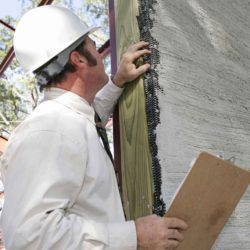 A building inspector checking over incomplete stucco work on new construction. Focus on stucco work.